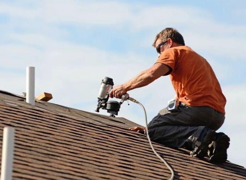 Монтажник покрывает крышу мягкой черепицей
